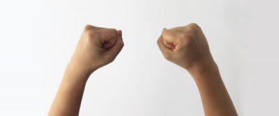 Manos arriba con puño cerado representando la fuerza de voluntad